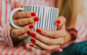 Woman in a red striped shirt holding a mug with red shellac gel polish